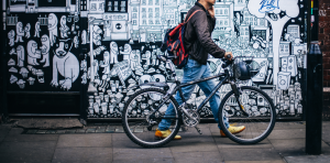 Man on the phone, walking with his bike